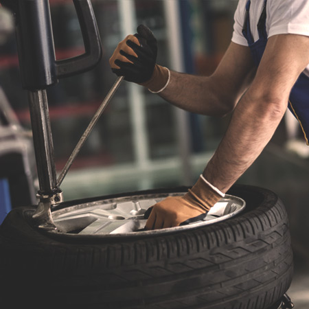 Man operating tire equipment that was purchased through auto repair shop loans
