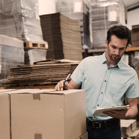 Man packaging new wholesale inventory inside a warehouse