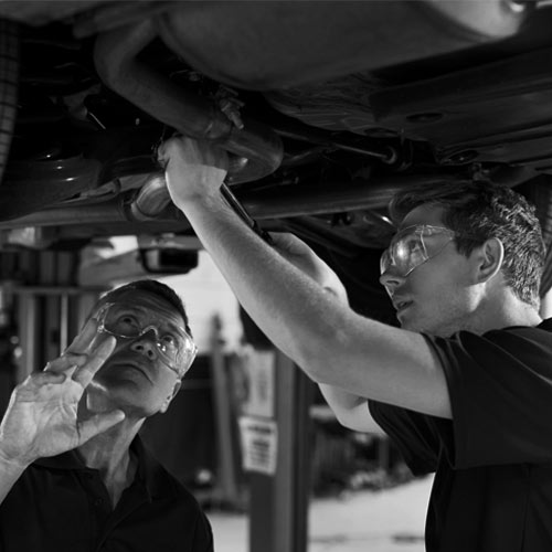 Automotive repair shop fixing an exhaust system on a vehicle