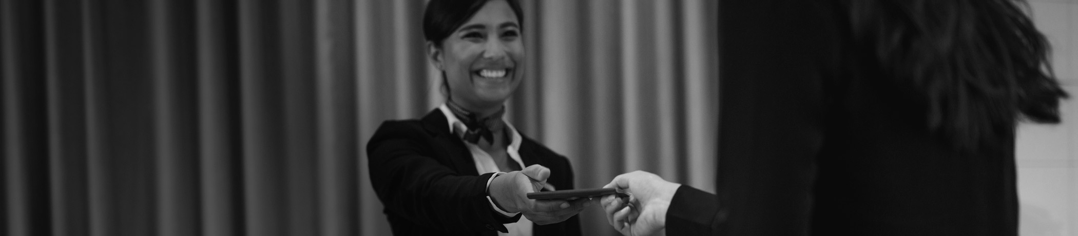 Hospitality worker checking in a guest at the front desk